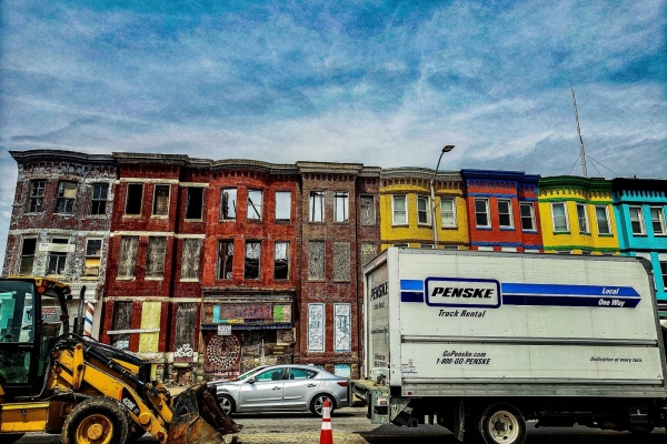Street with moving truck and construction equipment in front of multi-colored row houses