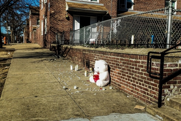 Stuffed bear and candles on sidewalk