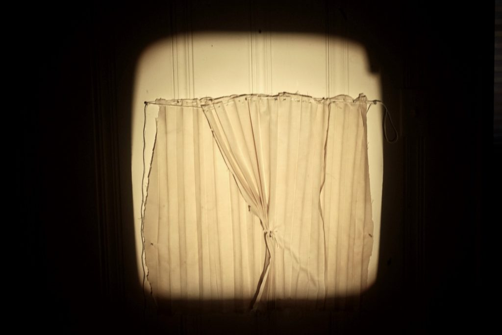 White curtains illuminated by a square of light