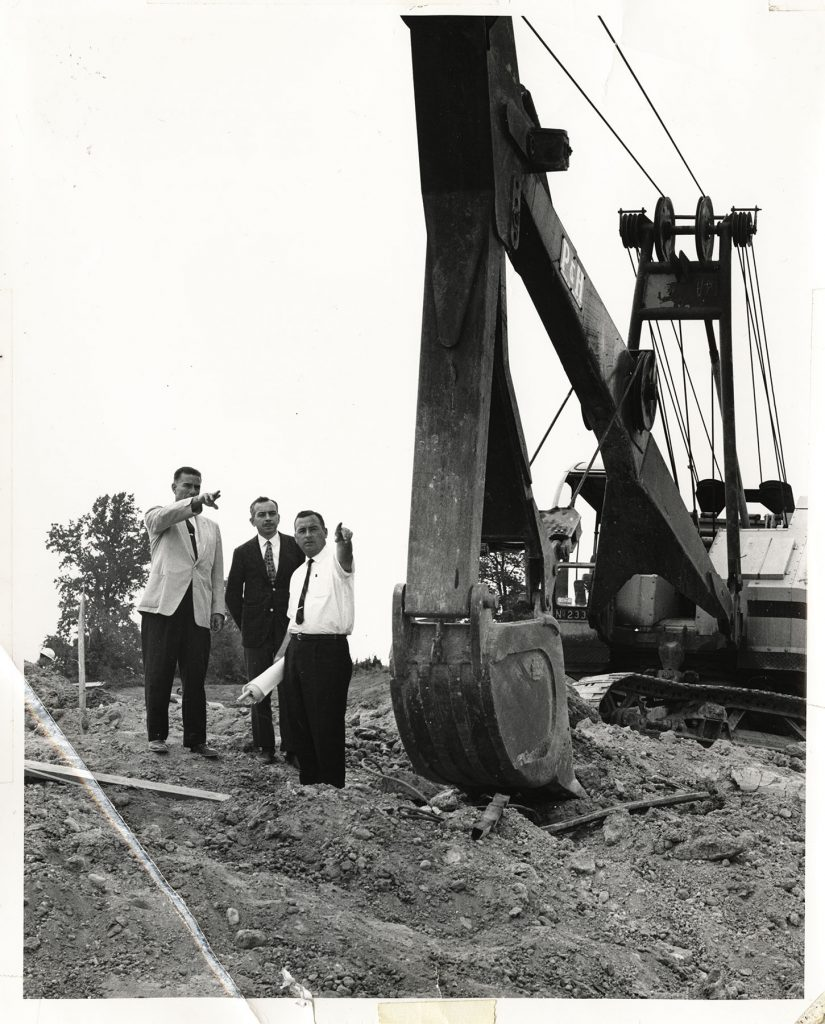 architects talking next to a ground digging crane