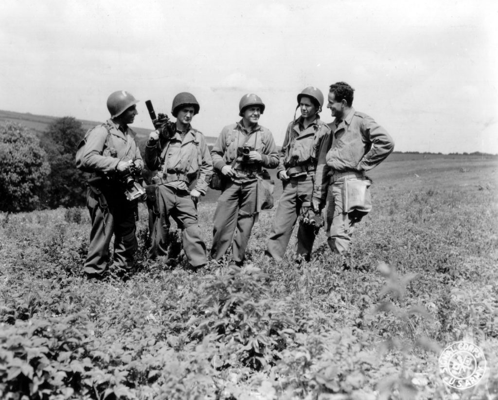 group of young man in army dress holding cameras in a hill