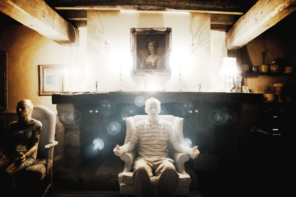 Man sitting in armchair with glowing white orbs surrounding him