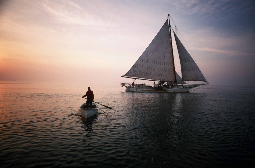 Man rowing dinghy away from sailboat