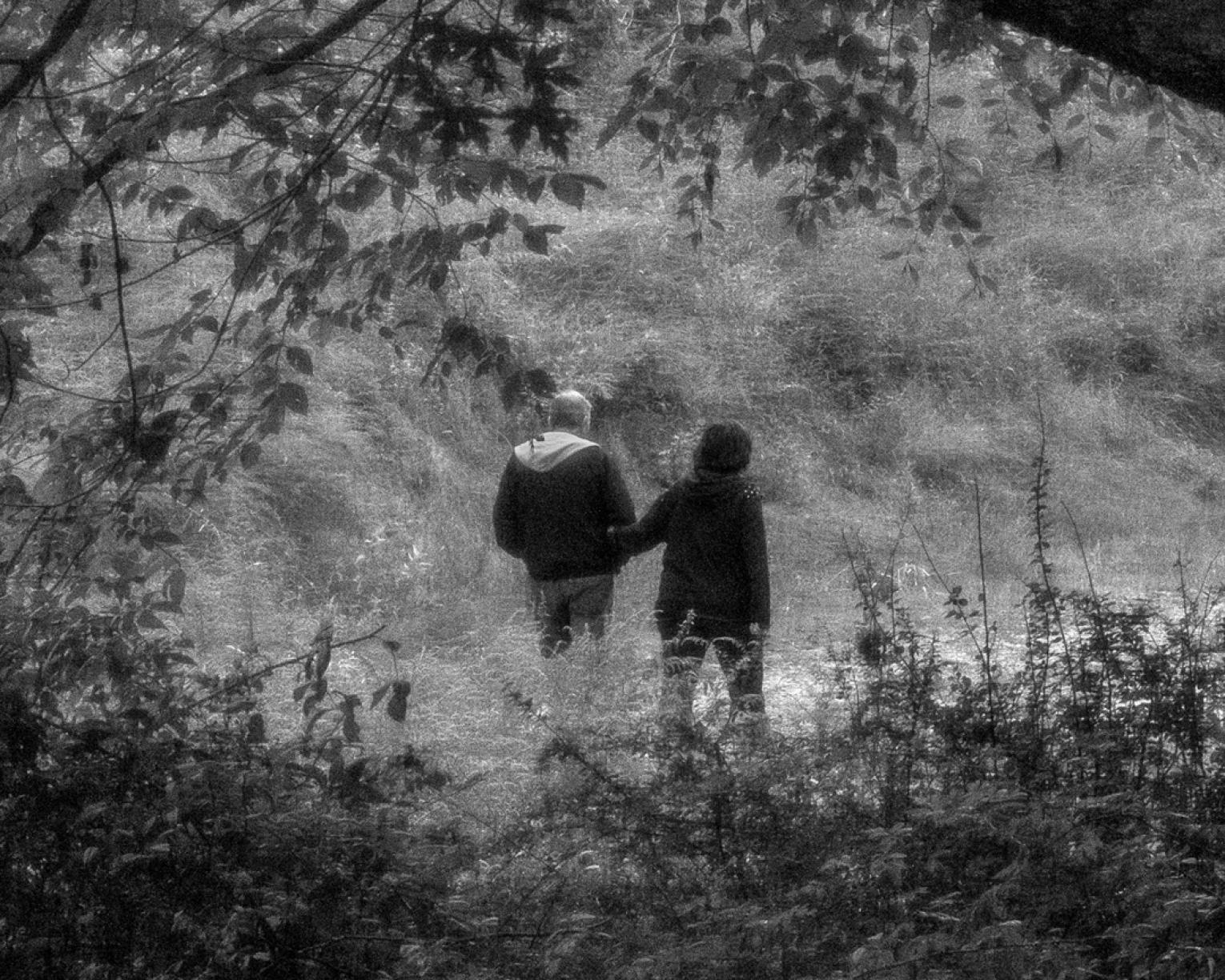 Black and white photo of a couple holding hands and walking in nature