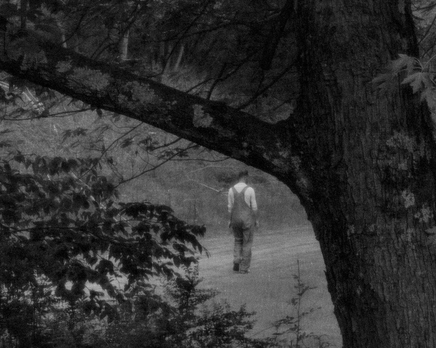 Black and white photo of man in overalls walking down dirt road