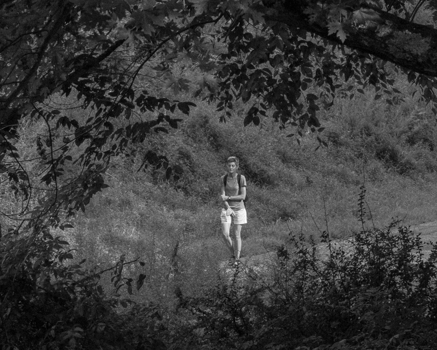 Black and white photo of woman in shorts walking alone on a gravel road; she grasps her arm with her hand