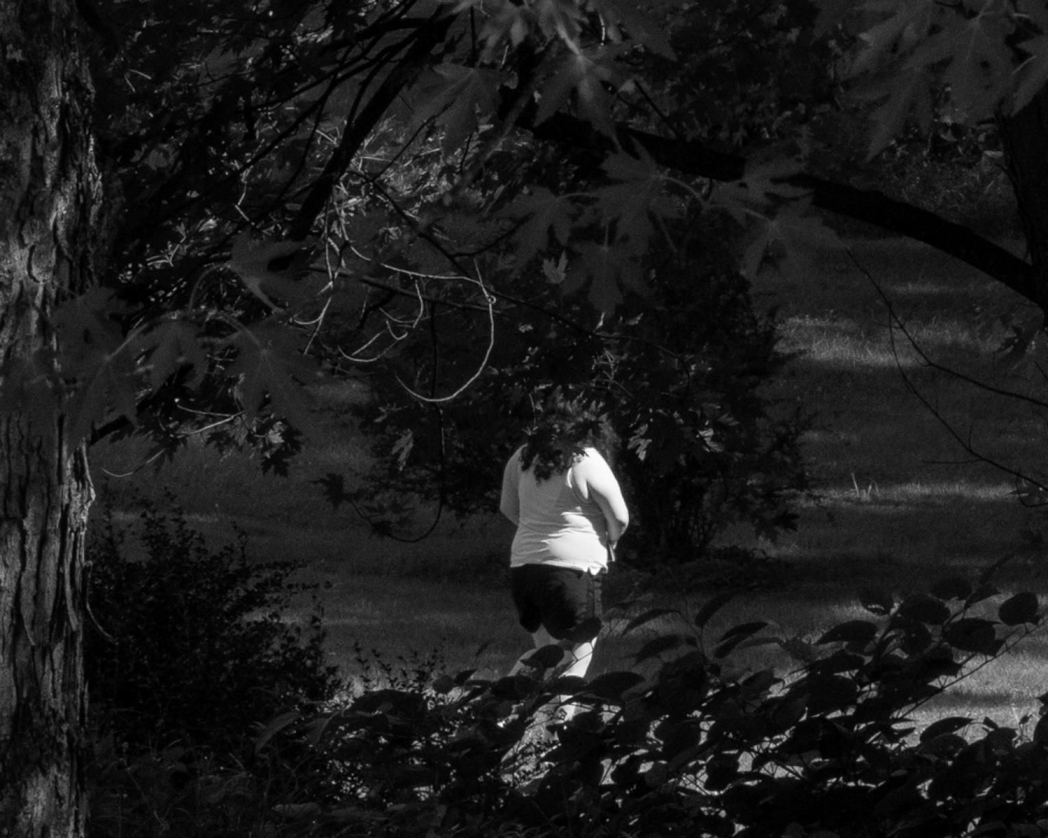Black and white phot of a woman walking in shadows of trees and leaves