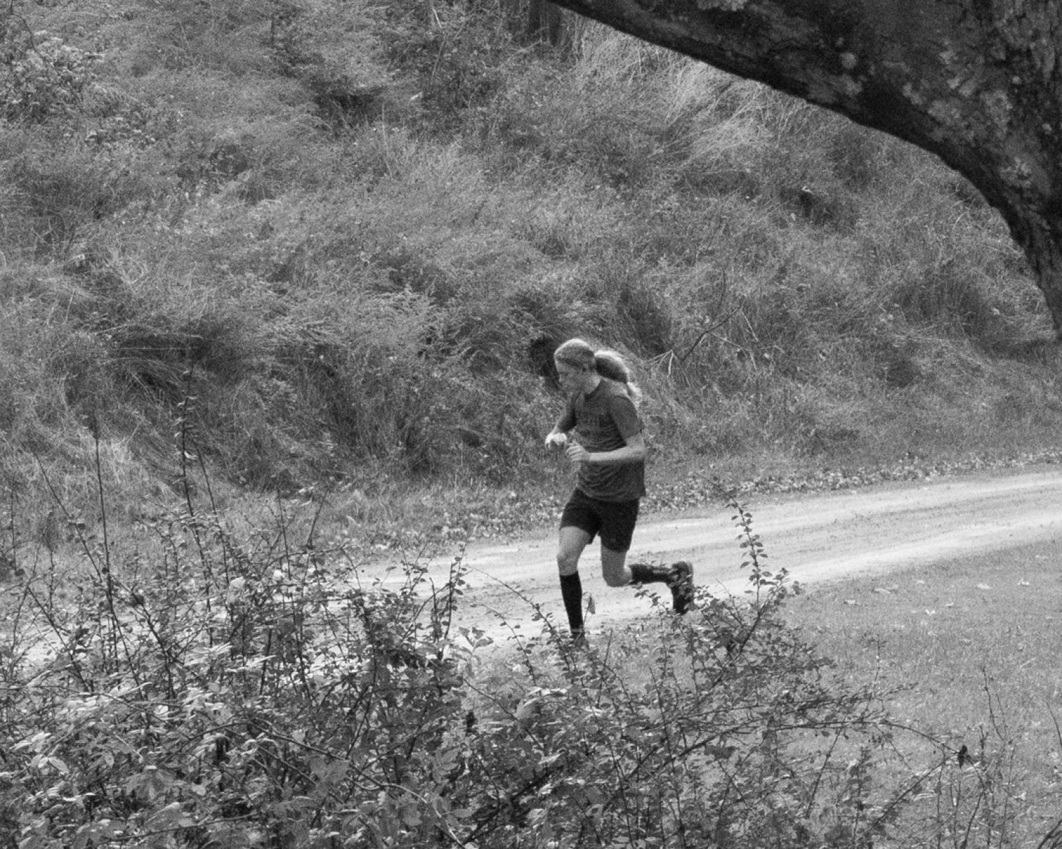 Black and white photo of person jogging along dirt road
