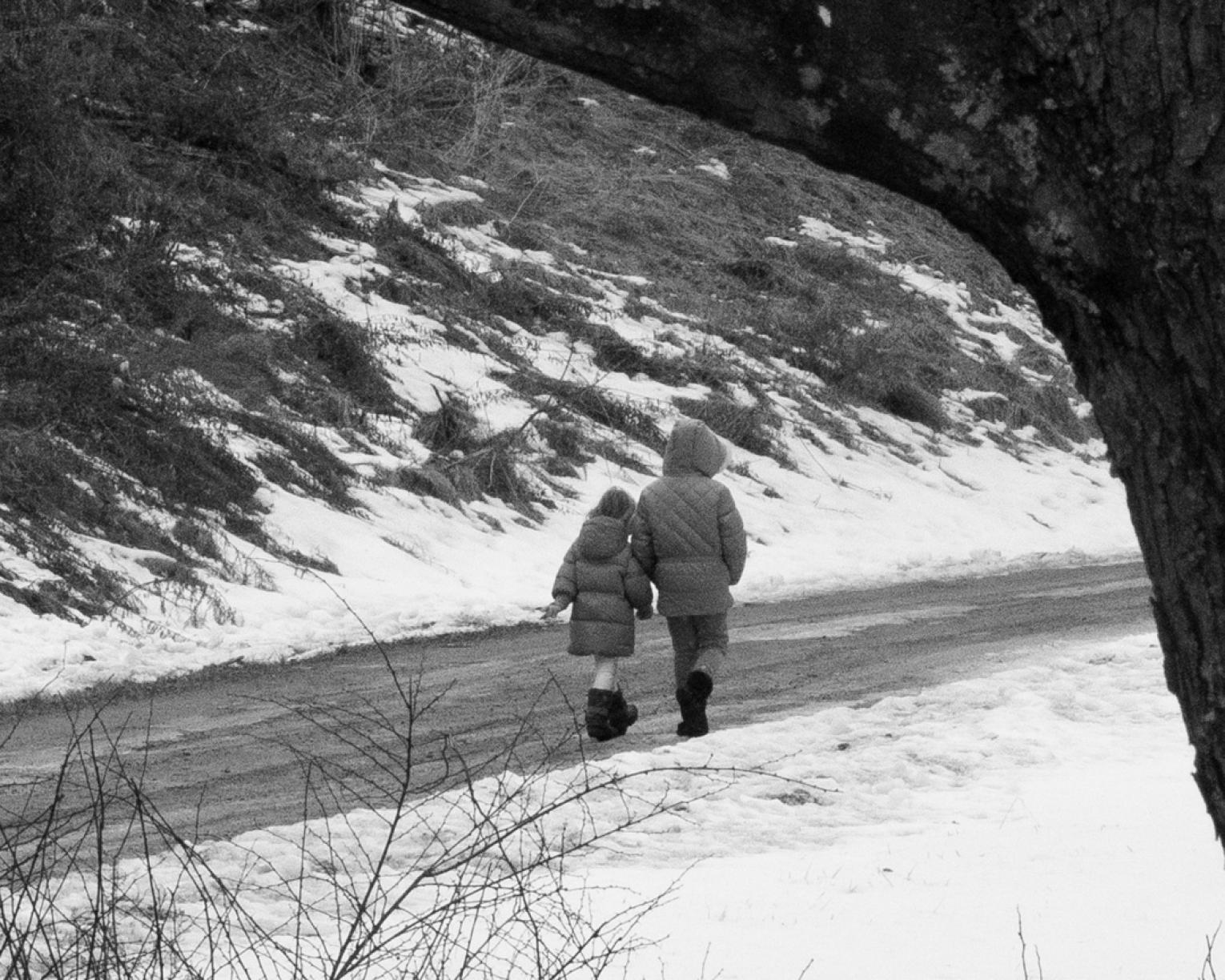 Black and white photograph of two girls walking on snowy gravel road