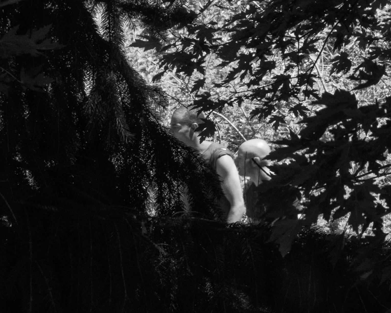 Black and white photo of two men walking through foliage