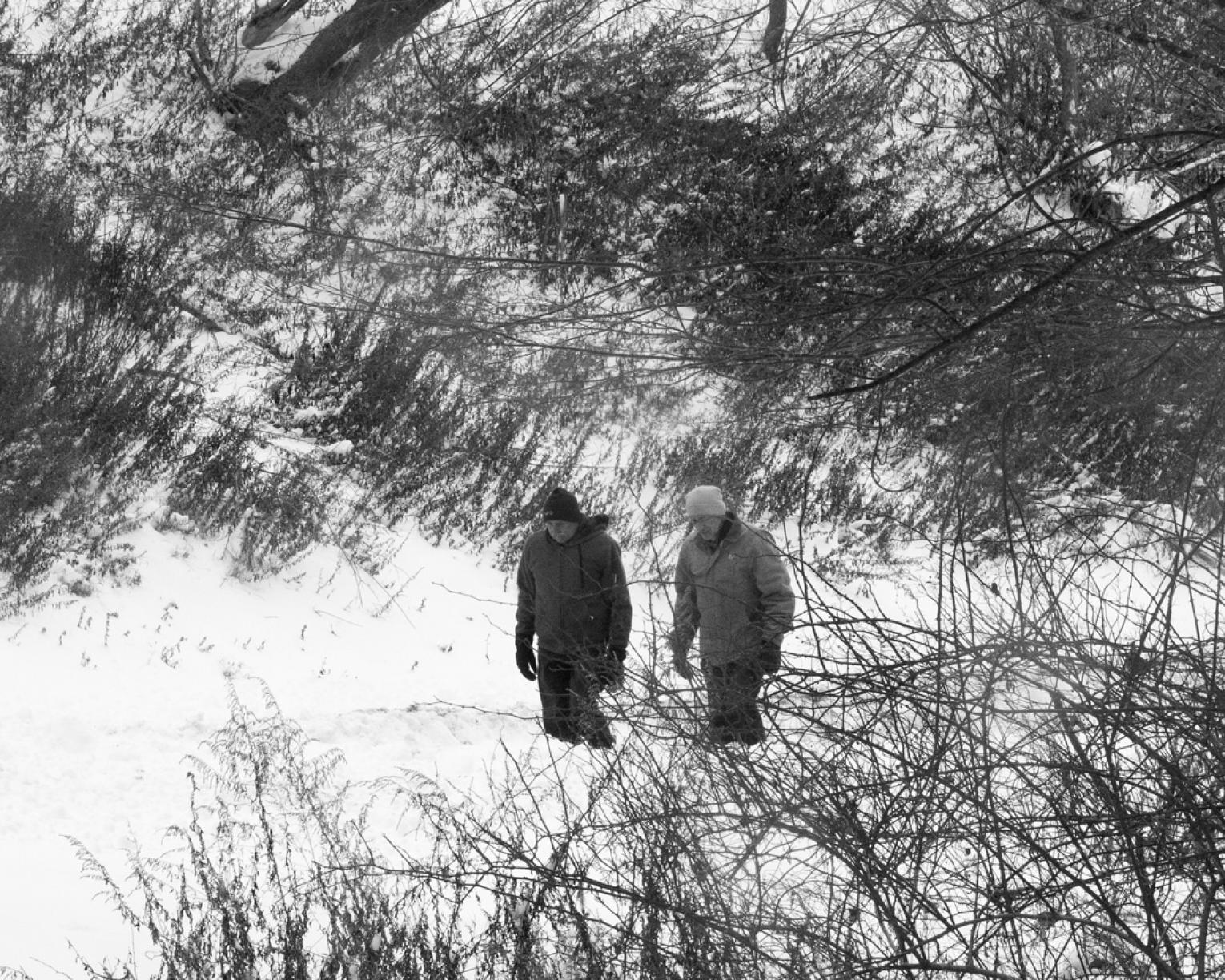 Black and white photograph of two men walking on snowy road