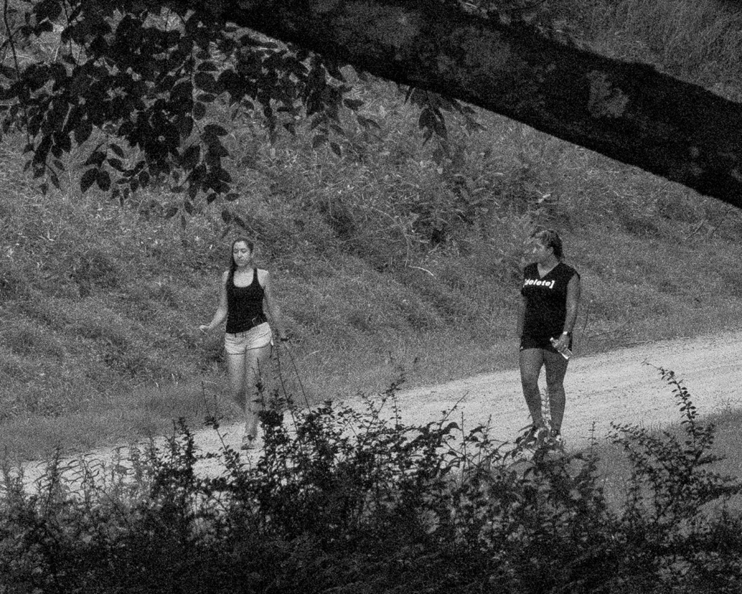 Black and white photo of two women walking down the road; one wears a shirt that says