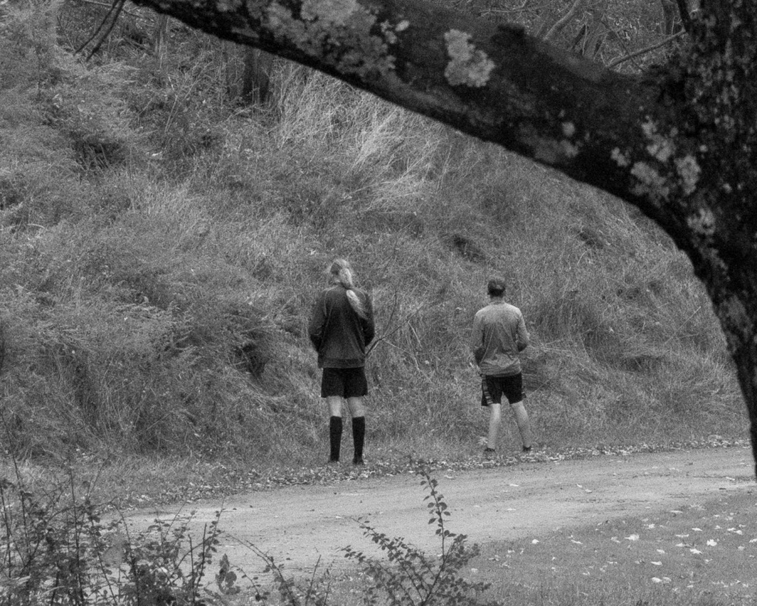 Black and white photo of two figures standing on the road looking into nature