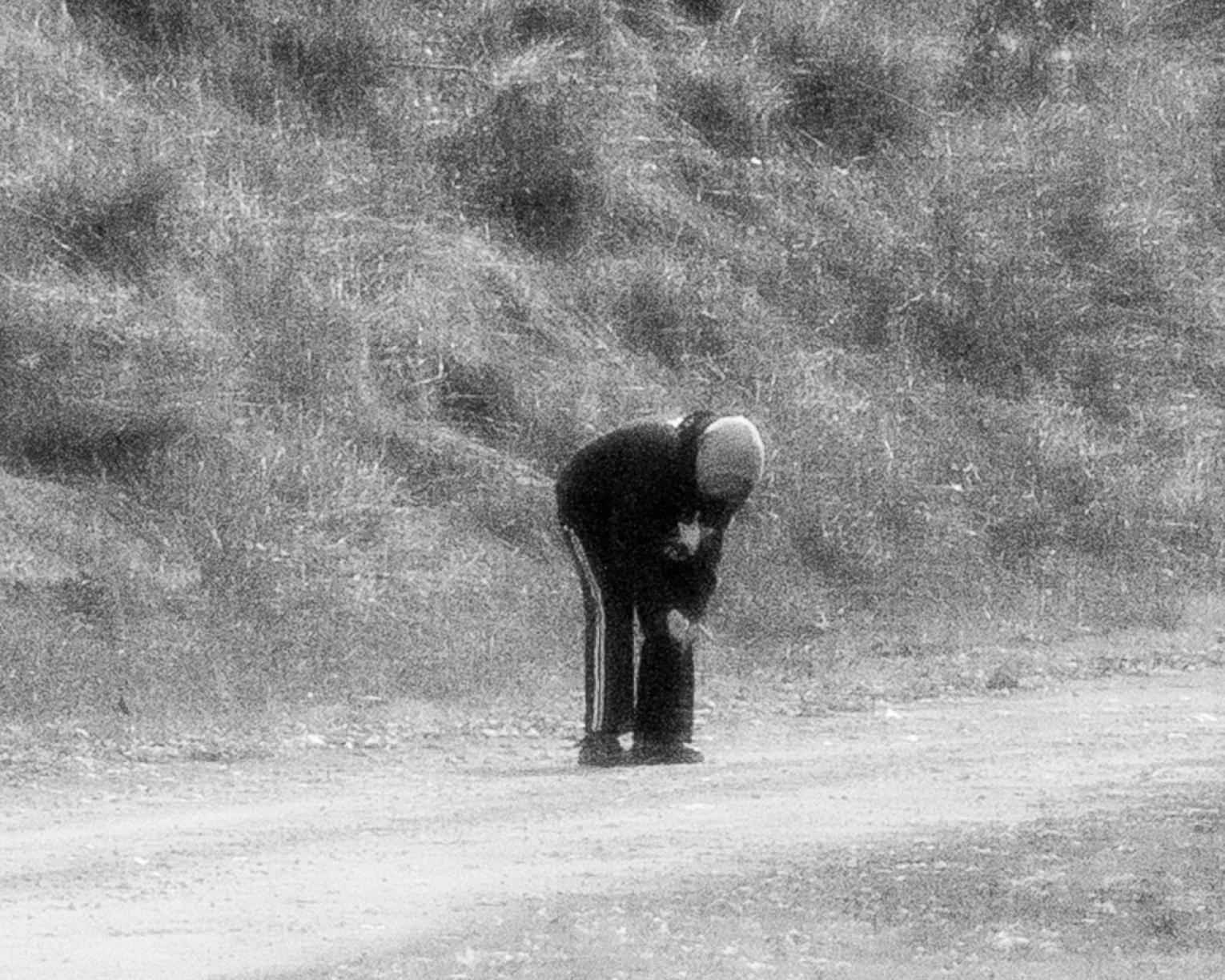 Black and white photo of person bent over to look at something in the road