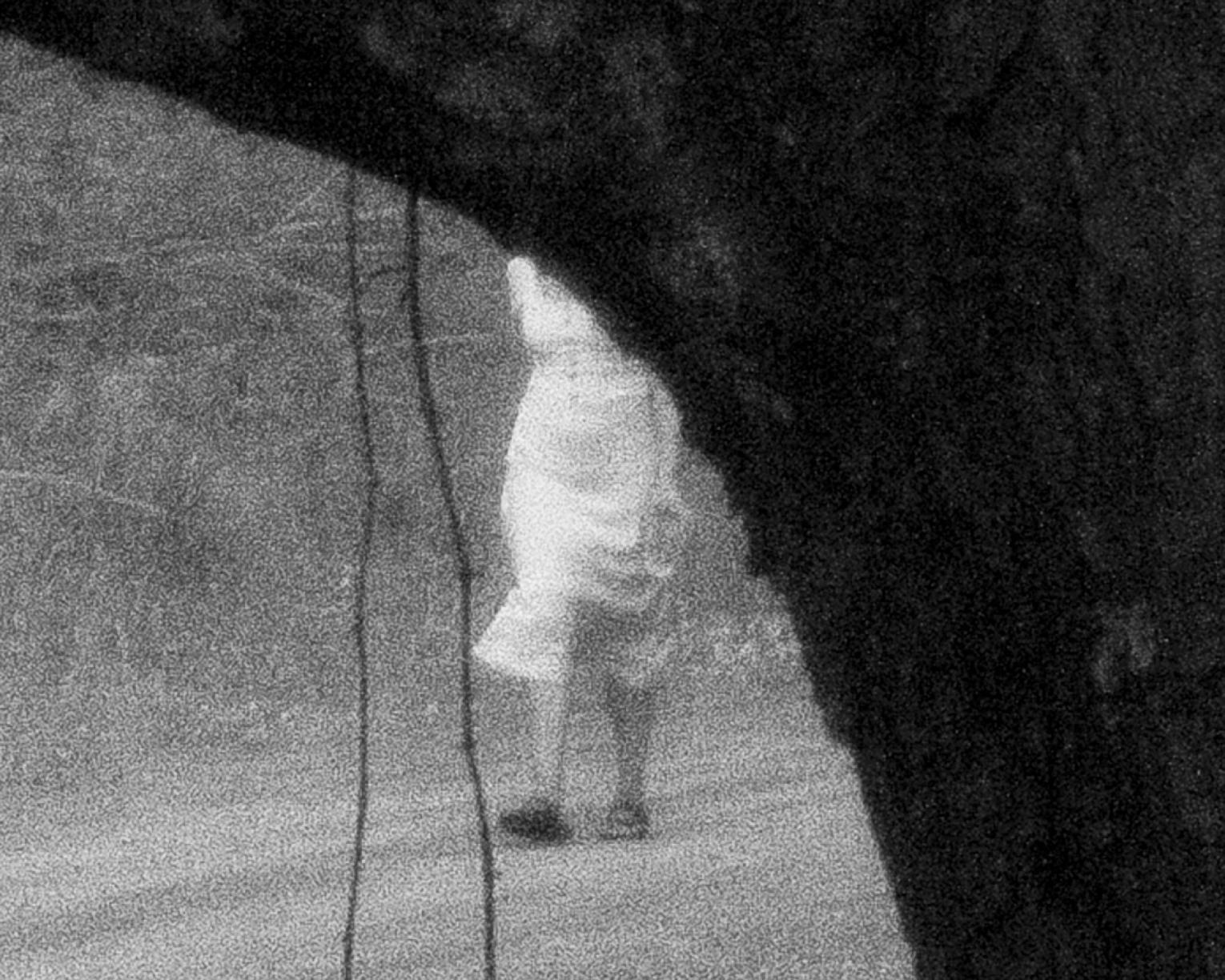Black and white photo of person in a white dress holding a glass, partially obscured by tree limb