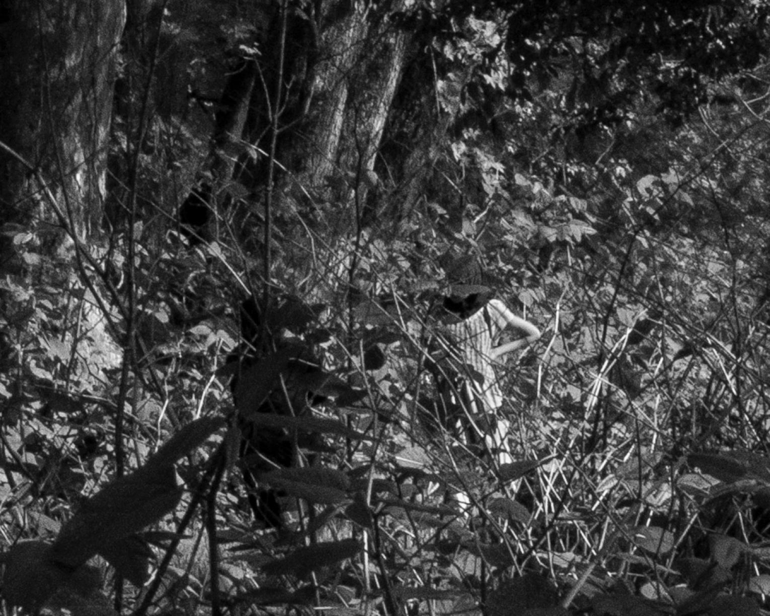 Black and white photo of a woman standing amidst foliage